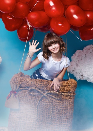 baby girls smiley face: Small cute girl with beautiful face on a board with a lot of red balloons having heart form on  top flying in happy mood under bright blue sky with clouds and wind playing with her hair Valentines day