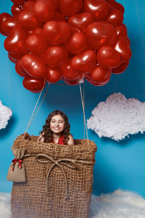 farytale: Small cute girl with beautiful face on a board with a lot of red balloons having heart form on  top flying in happy mood under bright blue sky with clouds and wind playing with her hair Valentines day