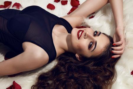 l�piz labial: Hermosa chica morena en toda su belleza con maquillaje de noche de oro y el l�piz labial de color rojo con el pelo oscuro en las pieles blancas y p�talos de rosas rojas en el cuerpo negro y sonriendo con toda su belleza Foto de archivo