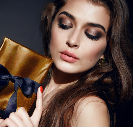 bonny: Beautiful young sexy brunette woman with bright evening make-up perfect smooth skin cosmetics cream face care, jewelry, beauty salon, magazine, close-up portrait with box present