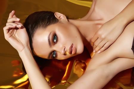 maquillaje de ojos: Joven y bella mujer de noche sexy maquillaje ojo pesta�as oscuras te�ido olas morena hombro desnudo pelo apilados Golden Tan mira en el artista de maquillaje belleza camera cosm�tico sal�n spa
