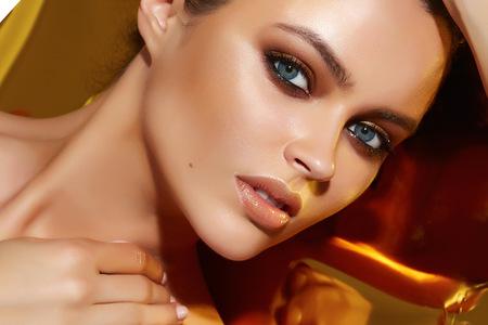 Mooie sexy jonge vrouw 's avonds make-up donker oog wimpers geverfd brunette golven gestapeld haar naakt schouder Golden Tan kijkt in de camera make-up artist cosmetica schoonheidssalon spa