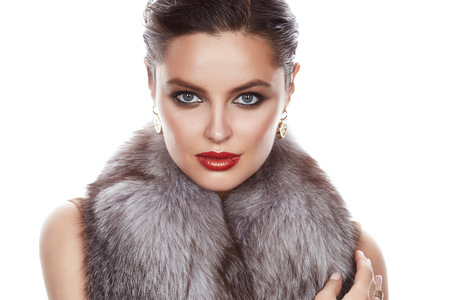 secular: Beautiful young sexy brunette with bright evening make-up red lips, wearing a slinky silk dress and cloak of fox fur, gold earrings and a ring on his hand, wealth and luxury, party Stock Photo