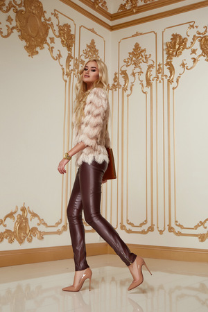 patent leather: Beautiful young sexy woman with long blonde curly hair thin slender with evening make-up wearing a tight leather pants pink blouse patent leather high-heeled shoes in hand holding bags clutches party