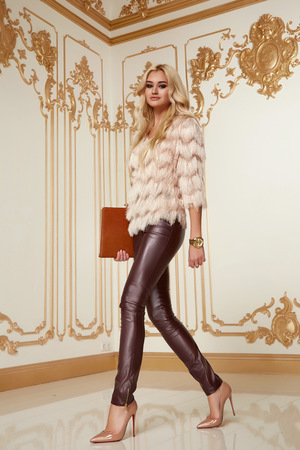 long pants: Beautiful young sexy woman with long blonde curly hair thin slender with evening make-up wearing a tight leather pants pink blouse patent leather high-heeled shoes in hand holding bags clutches party
