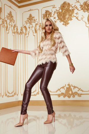 clutches: Beautiful young sexy woman with long blonde curly hair thin slender with evening make-up wearing a tight leather pants pink blouse patent leather high-heeled shoes in hand holding bags clutches party
