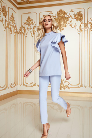 Beautiful sexy young blonde girl with long thick wavy hair thin slender figure perfect body and pretty face make-up wearing a light blue suit delicate high heels
