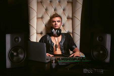 dj headphones: Young stylish trendy guy sitting musician DJ headphones for musical instruments and laptop with speakers