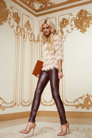secular: Beautiful young sexy woman with long blonde curly hair thin slender with evening make-up wearing a tight leather pants pink blouse patent leather high-heeled shoes in hand holding bags clutches party