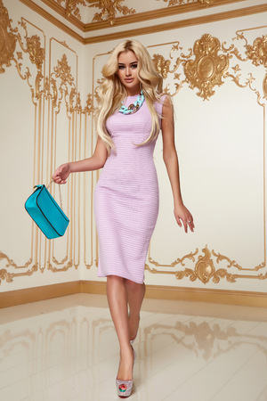 slinky: Beautiful young sexy blond girl with long curly hair with a bright evening make-up, wearing a slinky silk pink dress high heels a little blue bag necklace, wealth and luxury, party background baroque Stock Photo