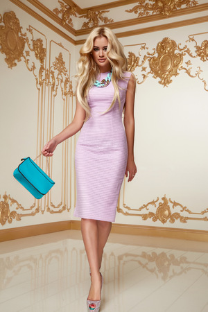 Beautiful young sexy blond girl with long curly hair with a bright evening make-up, wearing a slinky silk pink dress high heels a little blue bag necklace, wealth and luxury, party background baroque photo