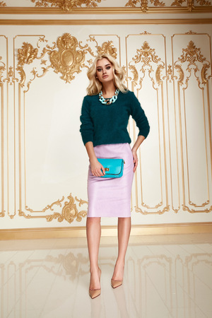 wavy hair: Beautiful sexy young blonde girl with long thick wavy hair thin slender figure perfect body and pretty face make-up wearing pink skirt green sweater small bag high heels.