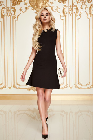 Beautiful sexy young blonde girl with long thick wavy hair thin slender figure perfect body and pretty face make-up wearing a little black dress high heels photo