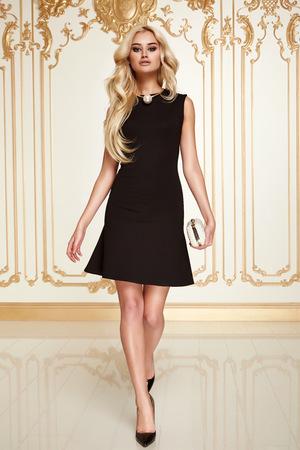 Mooie sexy jonge blonde meisje met lang dik golvend haar dunne slanke figuur perfect lichaam en mooie gezicht make-up dragen van een kleine zwarte jurk met hoge hakken
