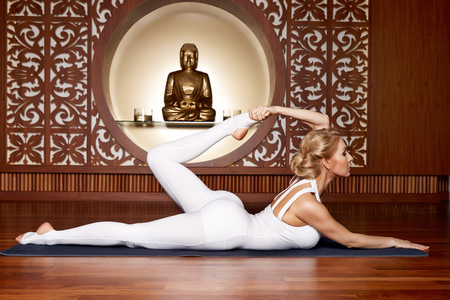 slinky: Beautiful young sexy blond girl with a sporty physique slender figure doing yoga exercises  fitness in slinky suit meditates relaxes pilates