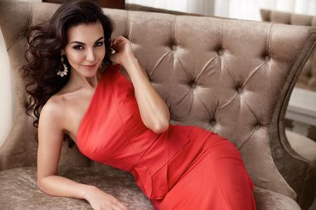 femme brune sexy: Belle sexy jeune femme brune aux longs cheveux ondulés mince mince chiffre corps parfait et joli visage maquillage porter une soirée robe rouge maigre et bijoux