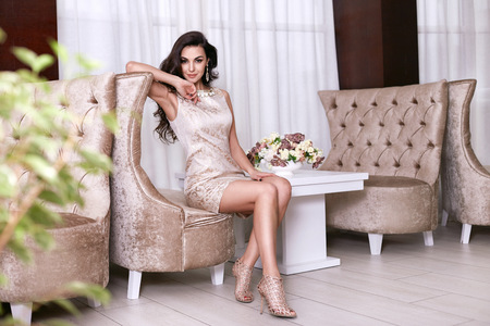 Beautiful sexy young brunette woman with long wavy hair thin slender figure perfect body and pretty face make-up wearing a beige evening skinny dress and jewelry.