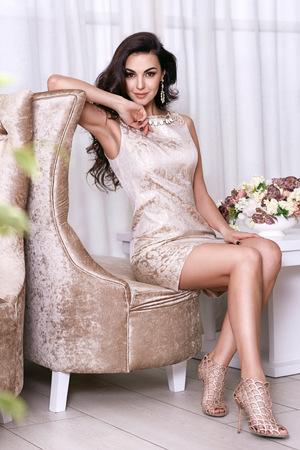 長いウェーブのかかった髪の美しいセクシーな若いブルネットの女性、ほっそりパーフェクトボディが薄くて細いドレスや宝石を夜ベージュを着て