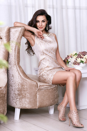 body jewelry: Beautiful sexy young brunette woman with long wavy hair thin slender figure perfect body and pretty face make-up wearing a beige evening skinny dress and jewelry