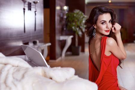 donna ricca: Bella sexy giovane donna bruna con i capelli ondulati lunghi snello sottile figura corpo perfetto e bel viso make-up che indossa un abito da sera rosso magro e gioielli Archivio Fotografico