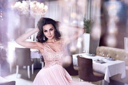長いウェーブのかかった髪の美しいセクシーな若いブルネットの女性、ほっそりパーフェクトボディが薄くて細いドレスや宝石を夕方ピンク着て、