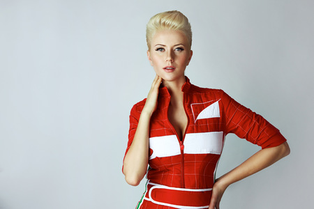 Portrait of a beautiful young sexy blond woman with short hair with a gentle make-up wearing a slinky red dress sporting well-groomed body and face golden tan Stock Photo