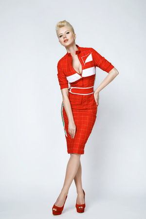 Portrait of a beautiful young sexy blond woman with short hair with a gentle make-up wearing a slinky red dress sporting well-groomed body and face golden tan photo