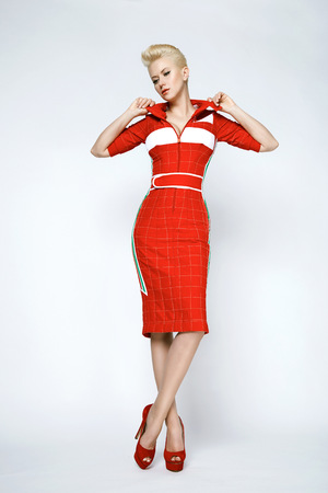 slinky: Portrait of a beautiful young sexy blond woman with short hair with a gentle make-up wearing a slinky red dress sporting well-groomed body and face golden tan Stock Photo
