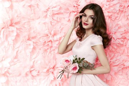 完璧な夏の日焼け薄い図を保持している花のピンク色の短いドレスに身を包んだ明るい夜メイク ブルネットの長いウェーブのかかった髪と美しい若