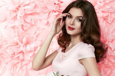 밝은 저녁 메이크업 완벽한 여름 긴 물결 모양의 갈색 머리를 가진 아름다운 젊은 섹시한 여자 꽃 분홍색을 들고 색 짧은 드레스를 입고 황갈색 얇은