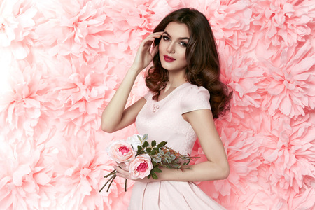 spring fashion: Beautiful young sexy girl with long wavy brunette hair with a bright evening make-up perfect summer tan thin figure dressed in colored short dress holding flower pink