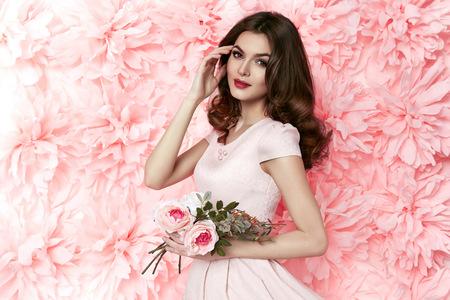 Gyönyörű fiatal szexi lány, hosszú hullámos barna haja fényes esti smink tökéletes nyári barnaság vékony alak öltözött színes rövid ruhát gazdaság virág pink