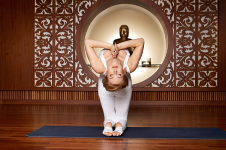 slinky: Beautiful young sexy blond girl with a sporty physique slender figure doing yoga exercises fitness in slinky suit meditates relaxes pilates Stock Photo
