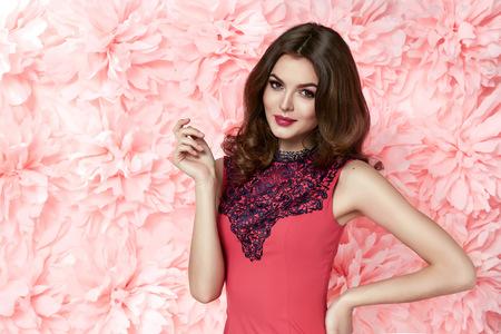 Krásná mladá sexy dívka s dlouhými vlnitými vlasy brunetka s jasným večerním make-up perfektní letní opálení tenký postava oblečená v barevném krátké šaty hospodářství květina růžová