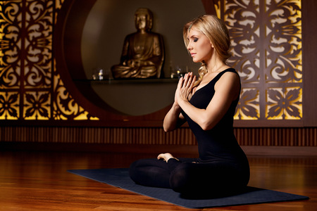 buddha lotus: Beautiful young sexy blond girl with a sporty physique slender figure doing yoga exercises  fitness in suit meditates relaxes pilates