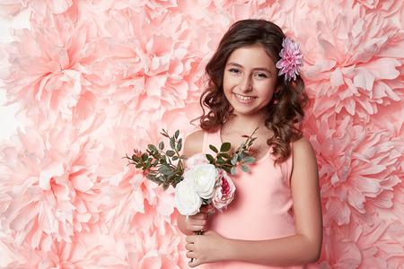 Schöne junge Mädchen mit dem langen wellenförmigen Haar brünett mit einem hellen Abend Make-up perfekte Sommerbräune dünne Gestalt in farbigen kurzen Kleid gekleidet, hält Blume rosa