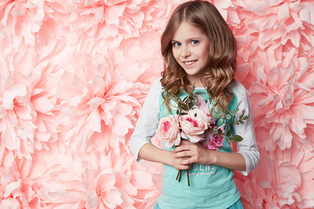 Beautiful young little girl with long wavy brunette hair with a bright evening make-up perfect summer tan thin figure dressed in colored short dress holding flower pink Reklamní fotografie - 38621939