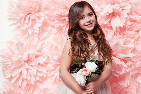 short hairs: Beautiful young little girl with long wavy brunette hair with a bright evening make-up perfect summer tan thin figure dressed in colored short dress holding flower pink