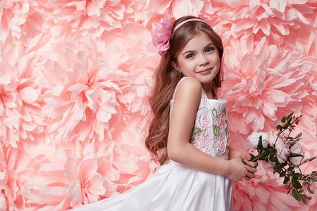 petite fille avec robe: Belle jeune petite fille avec brune cheveux longs ondul�s avec une soir�e brillante maquillage �t� parfait silhouette mince tan habill� en robe courte couleur tenant une fleur rose Banque d'images