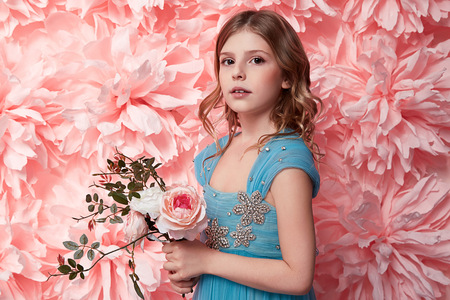 tights: Beautiful young little girl with long wavy brunette hair with a bright evening make-up perfect summer tan thin figure dressed in colored short dress holding flower pink