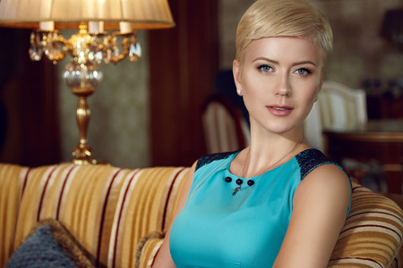 baroque room: Beautiful young sexy blonde with short hair exquisite evening make-up sitting in a room with an interior in blue fashionable stylish dress bare shoulders lamp sofa Baroque