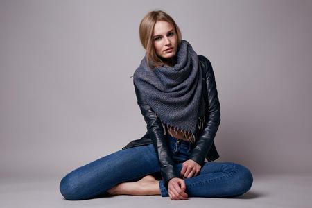 ナチュラルメイクの身に着けているジーンズとレザー ジャケット服カタログの春コレクションのスタイルとファッションの床モデルの上に座って長 写真素材