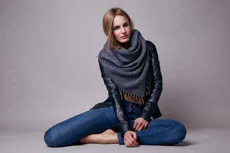 Beautiful young sexy woman with long blonde hair with natural make-up wearing jeans and leather jacket sitting on the floor model with a clothing catalog spring collection style and fashion Foto de archivo