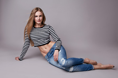 Beautiful young sexy woman with long blonde hair with natural make-up wearing jeans and pirates top sitting on the floor model with a clothing catalog spring collection style and fashion