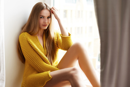 Beautiful young sexy woman with long blonde hair with natural make-up wearing Sweater sun tan body skin pure natural sitting next to window model with clothing catalog spring collection fashion style