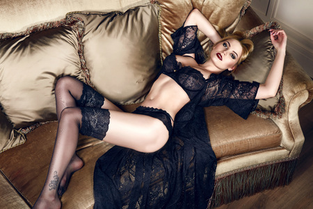 Beautiful sexy tanned blond woman with  in black lace lingerie with a beautiful evening makeup on the sofa hand strap with shoulder red lips perfect body Stock Photo