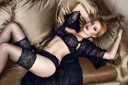 ladies underwear: Beautiful sexy tanned blond woman with  in black lace lingerie with a beautiful evening makeup on the sofa hand strap with shoulder red lips perfect body Stock Photo