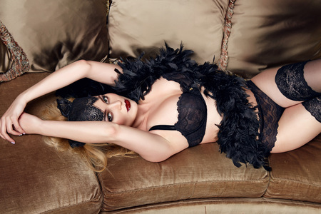 sconces: Beautiful sexy tanned blond woman with  in black lace lingerie with a beautiful evening makeup on the sofa hand strap with shoulder red lips perfect body Stock Photo