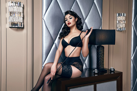 sconces: Beautiful sexy tanned brunette woman with  in black lace lingerie with a beautiful evening makeup sitting on the table next to wall hand strap with shoulder red lips perfect body Stock Photo