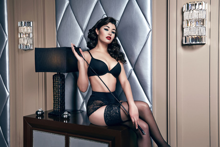 collarbone: Beautiful sexy tanned brunette woman with  in black lace lingerie with a beautiful evening makeup sitting on the table next to wall hand strap with shoulder red lips perfect body Stock Photo